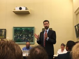 a slim, bearded man in a dark suit and red tie, Councilmember Charles Allen, stands at center against a yellow background. Audience members are looking at him. He gestures with two hands flat before him.