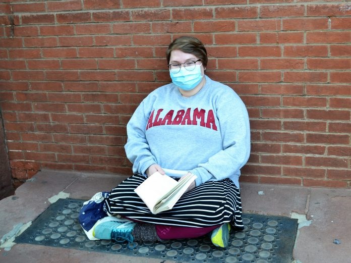 A woman sits cross-legged on ground with her back against a brick wall. She is wearing glasses and a hospital mask and holding a book.